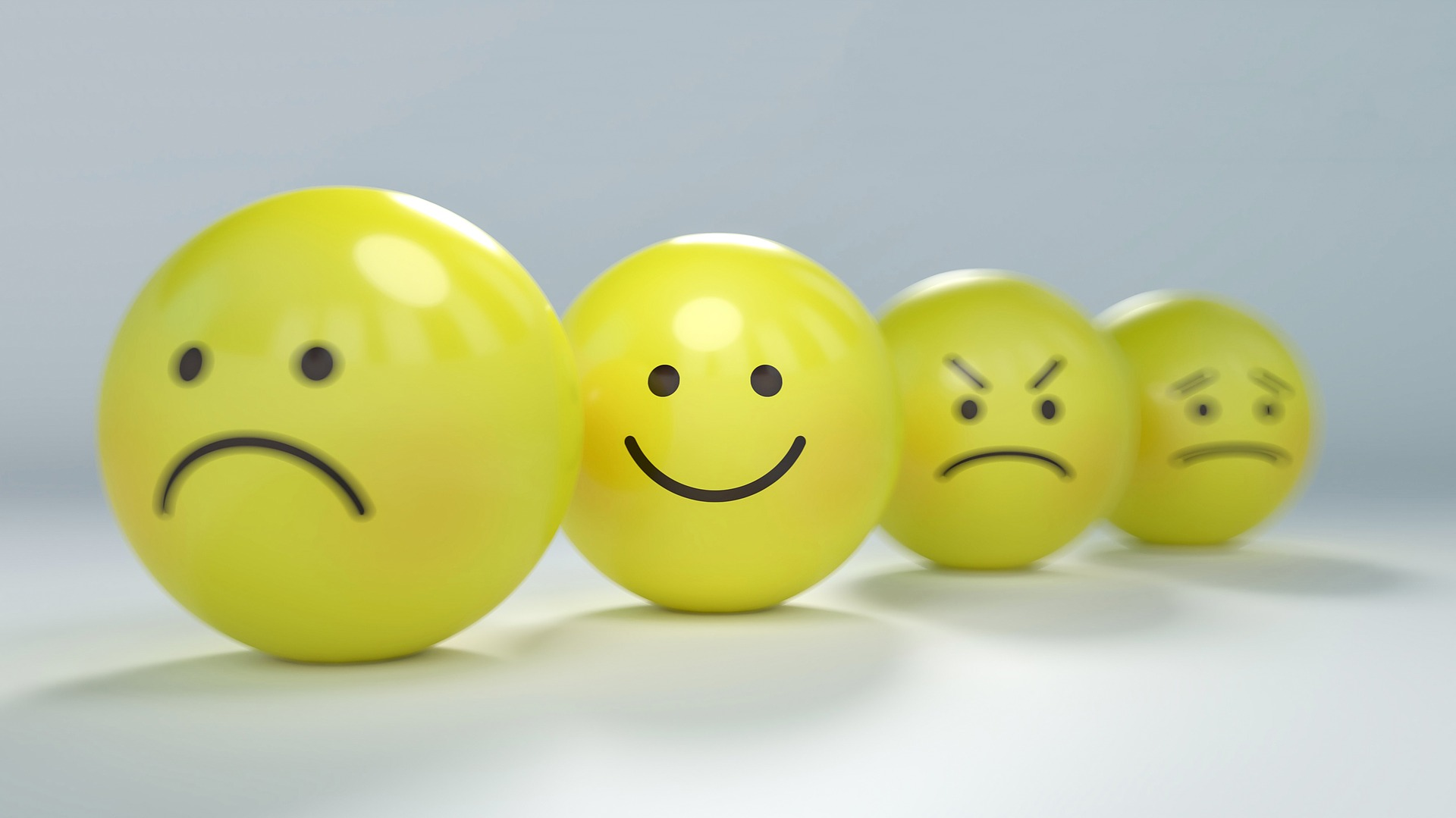 Four yellow smiley face balls in a row showing different emotions