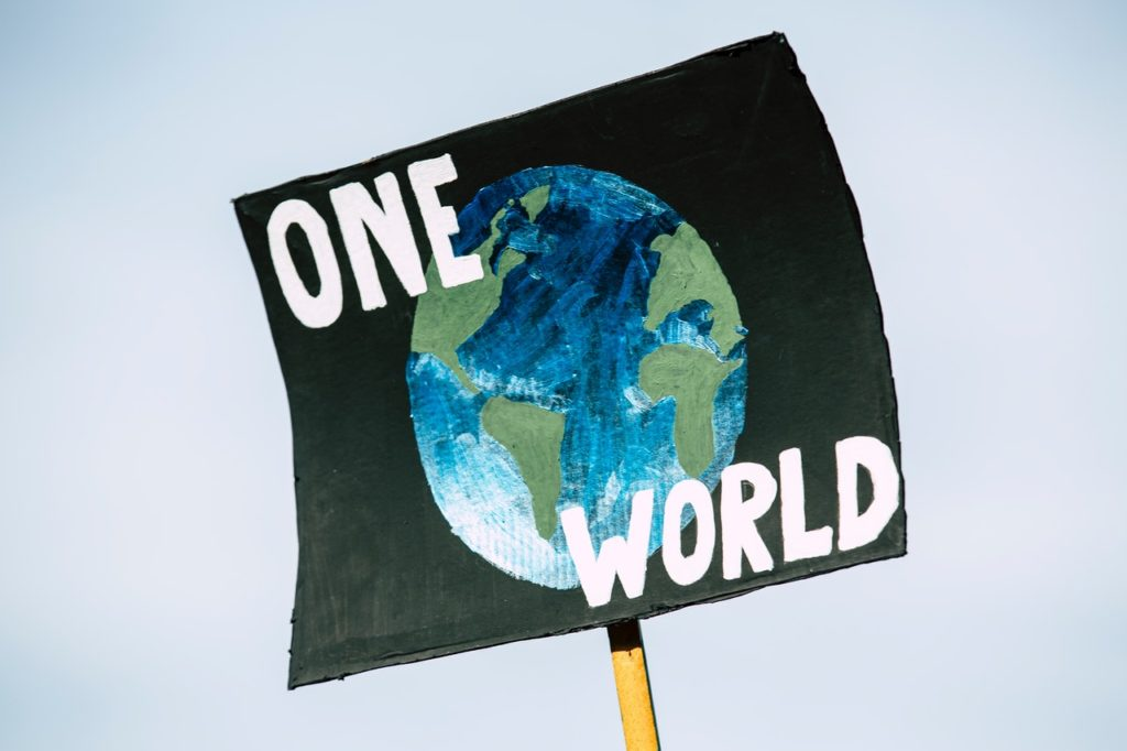 "Sign that says ""One World"" with the planet Earth depicted on it"